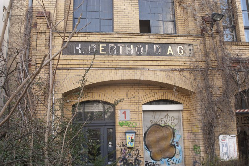 """Aside from the old Berthold factory building itself, the most visually appealing part of today's Mehringhof for those interested in the history of the foundry is the """"H. Berthold A.G."""" sign above Aufgang 1 [entrace 1]. Most of its letters have fallen off of the façade since the 1970s – or partially fallen off, in the case of the second H."""